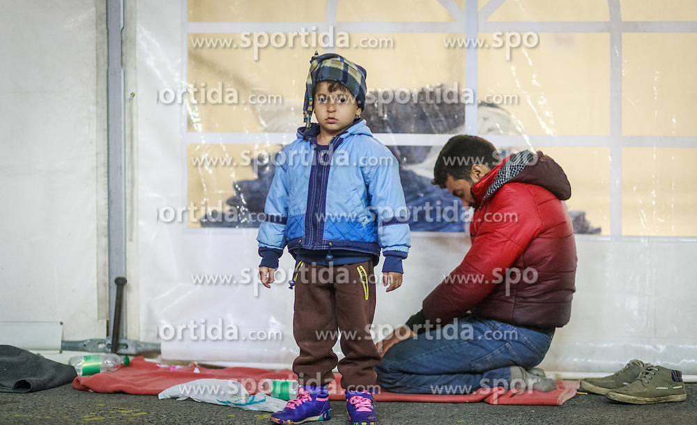 03.10.2015, Grenzübergang, Salzburg - Freilassing, GER, Flüchtlingskrise in der EU, im Bild ein Kind steht vor seinem betenden Muslimischen Vater // a child standing in front of his praying Muslim father. Europe is dealing with its greatest influx of migrants and asylum seekers since World War II as immigrants fleeing war and poverty in the Middle East, Afghanistan and Africa try to reach Germany and other Western European countries, German - Austrian Border, Salzburg on 2015/10/03. EXPA Pictures © 2015, PhotoCredit: EXPA/ JFK