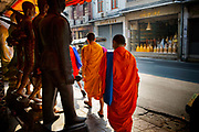 Monks walking past assorted religious figures and statues. Situated in the heart of Bangkok, near the famous swing, is a series of streets and alleyways dedicated to the manufacture of Buddhist and Hindu icons together with other religious paraphernalia.