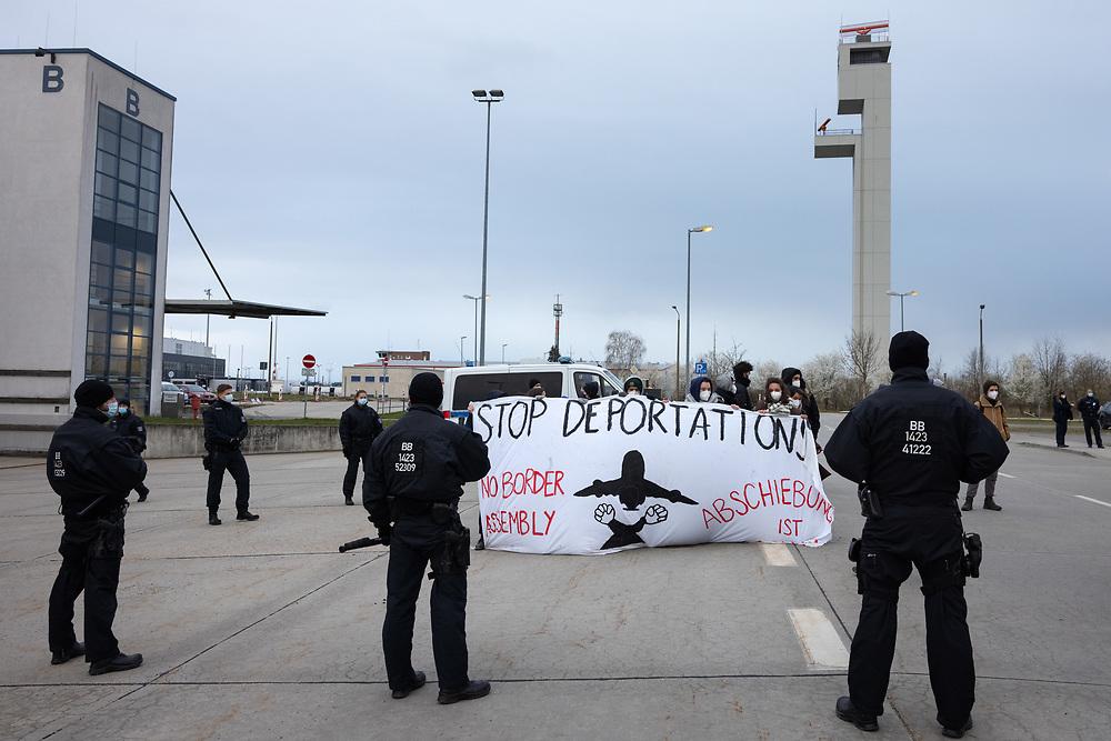 """Mehrere hundert Menschen protestieren auf einer Kundgebung des Berliner Bündnisses gegen Abschiebungen am Flughafen Berlin-Brandenburg BER gegen eine geplante Sammelabschiebung nach Afghanistan. Neben der angemeldeten Kundgebung finden auch Aktionen des zivilen Ungehorsams statt. Aktivisten blockieren ein Gebäude des Abschiebegefängnisses auf dem Flughafengelände und die Mittelstraße. Vor dem Abflug laufen die Demonstranten direkt zum Zaun am Terminal 5, vor dem sie von der Polizei mit Pfefferspray gestoppt werden. Trotz Protesten und Blockadversuchen startet der Charterflug nach Kabul gegen 21:30 Uhr. Demonstranten mit Banner """"Stop Deportation"""" auf dem Flughafengelände. Schönefeld, Deutschland, 07.04.2021.<br /> <br /> [© Christian Mang - Veroeffentlichung nur gg. Honorar (zzgl. MwSt.), Urhebervermerk und Beleg. Nur für redaktionelle Nutzung - Publication only with licence fee payment, copyright notice and voucher copy. For editorial use only - No model release. No property release. Kontakt: mail@christianmang.com.]"""