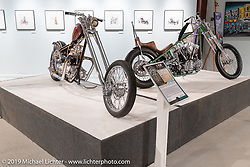 Bagger Nation's Paul Yaffe's Re-Cycled (L) custom 1964 Triumph Thunderbird 650 and Nick Pensebene's 3-Peat custom 1967 Shovelhead Chopper on view in the What's the Skinny Exhibition (2019 iteration of the Motorcycles as Art annual series) at the Sturgis Buffalo Chip during the Sturgis Black Hills Motorcycle Rally. SD, USA. Thursday, August 8, 2019. Photography ©2019 Michael Lichter.