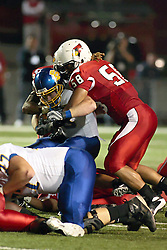 26 September 2009: Kelvyn Hemphill grabs Kyle Minett from behind and is assisted by Doni Phelps (58), stopping Minett's progress in a game which the South Dakota State Jackrabitts jump past the Illinois State Redbirds 38 - 17 at Hancock Stadium on campus of Illinois State University in Normal Illinois