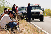 05 MAY 2003 -- SELLS, AZ:  Law Enforcement officers process a group of 11 undocumented immigrants from Mexico sitting on the edge of AZ highway 86 after being apprehended by the US Border Patrol. The immigrants were initially apprehended by the Tohono O'Odham police west of Sells, AZ, the capital of Tohono O'Odham Indian Reservation, May 5, 2003. The van was stopped for a traffic violation by the tribal police, who found the immigrants hiding inside. The driver of the van was arrested for driving without a license, no insurance and having false license plates. The Tohono OOdham reservation covers a vast expanse of Southern Arizona and has a 70 mile border with Mexico. In recent years the reservation has been flooded with undocumented immigrants who pass through the reservation on their way north to Phoenix, AZ, and other cities in the US. About 1,500 undocumented immigrants, most from Mexico, cross the reservation, which has more land than the state of Delaware,  every day. According to the tribal government, the tribal police department spends about 60 percent of its resources dealing with crime created by the undocumented immigrants. Many times tribal police officers have to wait hours for the US Border Patrol to respond to calls to pick up undocumented immigrants. The officer waited for more than an hour for Border Patrol to arrive on the scene and eventually released the immigrants. Border Patrol arrived minutes later and reapprehended all of the immigrants.  PHOTO BY JACK KURTZ