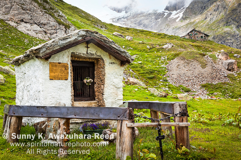 A small historic shrine at Val Veni. Rifugio Elisabetta is in the background. Alps, Italy, Europe, Summer.