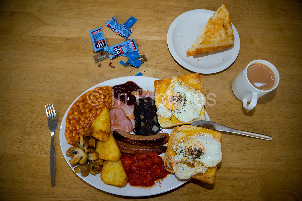 A giant full English breakfast with toast, black pudding, HP Sauce and a cup of tea on the 21st April 2011 in Shrewsbury in the United Kingdom.