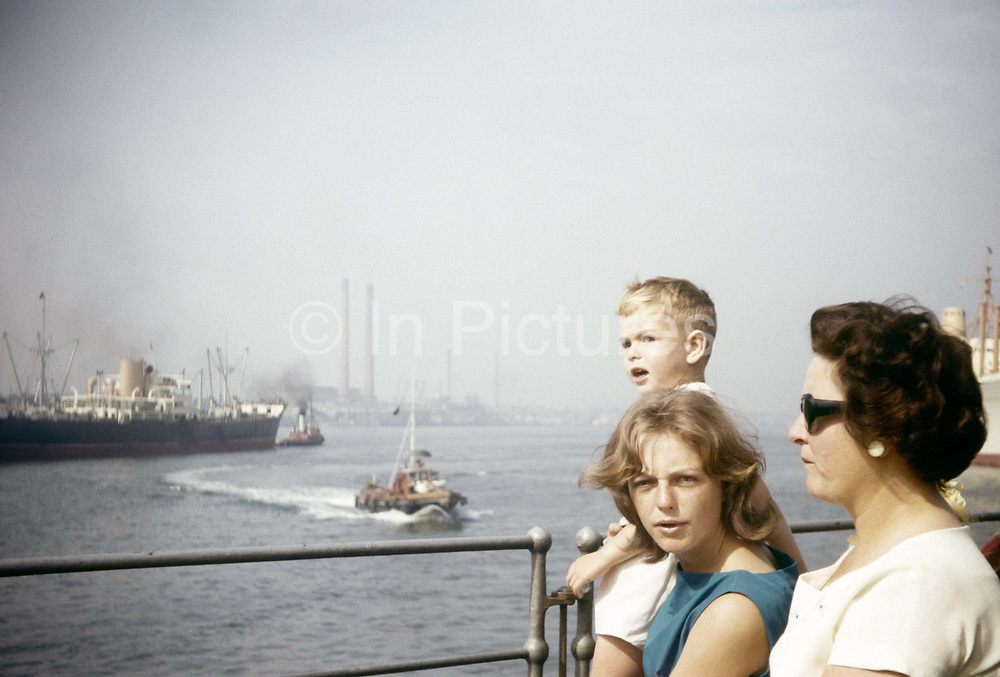 A family stand at railings watching shipping on the River Thames at Gravesend during summer time in the early 1960s. Standing at some railings, the two women and the young boy are looking out towards the River Thames at the Kent town just a few miles outside London. Here is shipping that is taking cargo to the capital in an era when the river still a main artery for goods brought from across the world into London. The picture was recorded on a film camera by the boy's father, an amateur photographer in 1962. The picture shows us a memory of nostalgia in an era from the last century.
