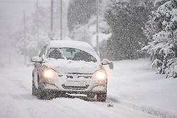 © Licensed to London News Pictures. 10/12/2017. Tring, UK. A car drives through heavy snow fall in the town of Tring in Buckinghamshire, England as parts of the south east of England are blanketed with snow for the first time this winter. Photo credit: Ben Cawthra/LNP