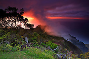The vibrant sunset shines through thick fog over the Kalalau Valley and the Pacific Ocean from the view at Pu`u o Kila lookout on the Hawaiian island of Kauai.