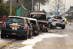 © Licensed to London News Pictures . 08/02/2013 . Salford , UK . Pictured a van understood to have been parked when the collision took place whilst behind under a green tarpaulin , the remains of a red Audi on its side . The scene on Leigh Road where a multi-vehicle pile up killed two , sparked a fire and damaged several cars and houses overnight , causing residents to be evacuated . Greater Manchester Police report seeing a stolen red Audi which they attempted to pursue prior to the crash . Photo credit : Joel Goodman/LNP