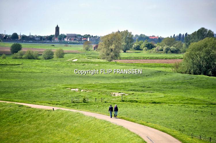 Nederland, Wamel, 3-5-2018Twee 50plussers, een man en vrouw, wandelen over de dijk langs de Waal.Foto: Flip Franssen