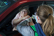Helen McCauley, left, of New Tripoli, gets a shot of the Moderna vaccine from registered nurse Caroline Spalding, right, during a COVID-19 drive-through vaccination clinic put on by Lehigh Valley Health Network on Jan. 27, 2021, at Dorney Park in Allentown, Pennsylvania. Community members 75 and older were eligible to receive their first dose with an appointment ahead of time. (Photo by Matt Smith)