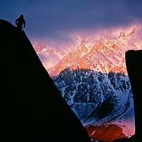 Sierra Nevada, California. Rock climber atop boulder in Buttermilk Rocks near Bishop.  Mount Tom background.