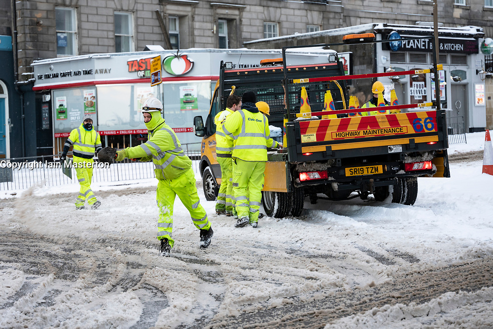 Edinburgh, Scotland, UK. 10 Feb 2021. Big freeze continues in the UK with heavy overnight and morning snow bringing traffic to a standstill on many roads in the city centre. Pic; Workers spread salt by hand on roundabout at Lothian road and Leith Walk. . Iain Masterton/Alamy Live news