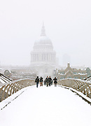 People walk in the snow across the Millenium Bridge with a view towards the dome of St Pauls Cathedral, London, UK
