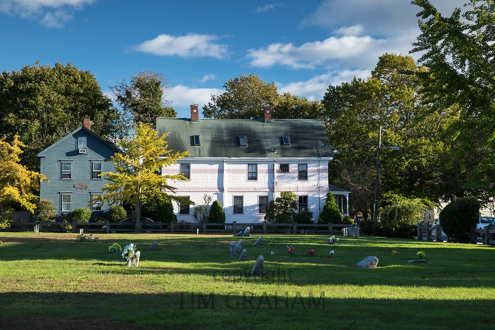 Typical traditional neat painted wooden clapboard houses with graves in cemetery in foreground in Newport, Rhode Island, USA