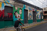 A man rides a bicycle by Sandinista revolutionary murals in Leon, Nicaragua. July 29, 2018.