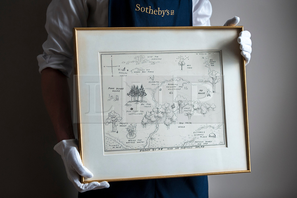 """© Licensed to London News Pictures. 31/05/2018. LONDON, UK. A gallery technician presents """"The Original Map of the Hundred Acre Wood"""", 1926, by E.H. Shephard (Est. GBP100,000-150-000), which will be offered for sale at Sotheby's in New Bond Street at the English Literature, History, Science, Children's Books and Illustrations sale on 10 July. A.A. Milne's much loved characters from the Winnie-the-Pooh books inhabited the Hundred Acre Wood.  Photo credit: Stephen Chung/LNP"""