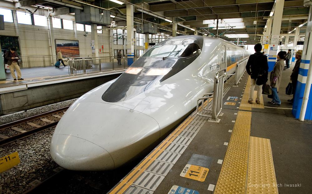 "A shinkansen (""bullet train"") arrives at Hiroshima station, Hiroshima Prefecture, Hiroshima, Japan. The high speed trains are the fastest in  Japan."