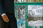 """A man in Maseru passes a faded poster for American Evangelist Ernest Angley's Miracle Crusade, which advertises """"AIDS and other death diseases healed""""."""