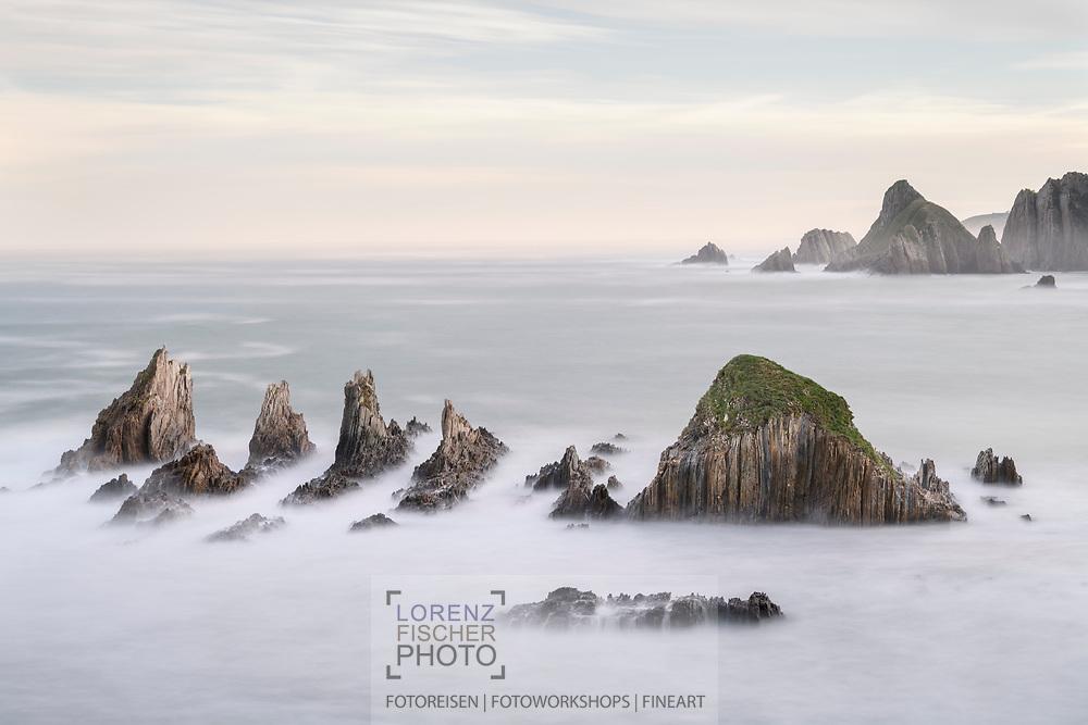 Dawn with red sky on a rocky coast with rock jags in the sea, Asturias, Spain<br /> <br /> <br /> <br /> Morgendämmerung mit Morgenrot an einer Felsküste mit Felszacken im Meer, Asturien, Spanien