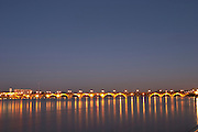The old Pont de Pierre bridge at night with reflections in Bordeaux on the Garonne River