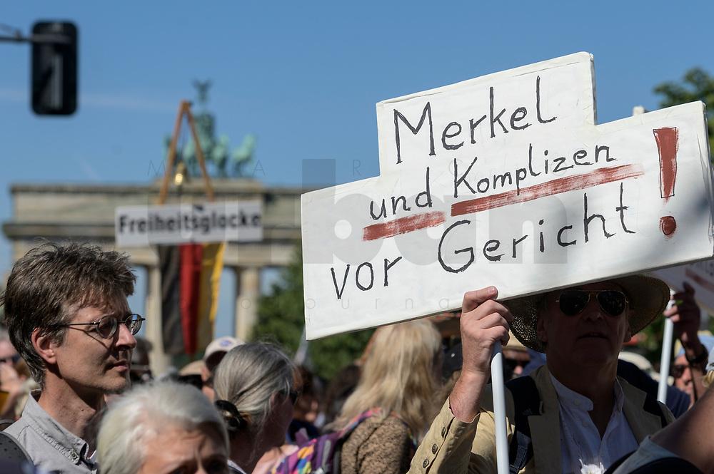 """01 AUG 2020, BERLIN/GERMANY:<br /> Mann mit Schild """"merkel und Komplizen vor Gericht"""", im Hintergrund das Bradenburger Tor, Demonstration gegen die Einschraenkungen in der Corona-Pandemie durch die Initiative """"Querdenken 711"""" aus Stuttgart unter dem Motto """"Das Ende der Pandemie - Tag der Freiheit"""", Unter den Linden<br /> IMAGE: 20200801-01-004<br /> KEYWORDS: Demo, Protest, Demosntranten, Protester, COVID-19, Corona-Demo"""