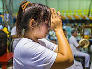 01 OCTOBER 2014 - BANGKOK, THAILAND: A woman prays at Wat Yannawa (also spelled Yan Nawa) during the Vegetarian Festival in Bangkok. The Vegetarian Festival is celebrated throughout Thailand. It is the Thai version of the The Nine Emperor Gods Festival, a nine-day Taoist celebration beginning on the eve of 9th lunar month of the Chinese calendar. During a period of nine days, those who are participating in the festival dress all in white and abstain from eating meat, poultry, seafood, and dairy products. Vendors and proprietors of restaurants indicate that vegetarian food is for sale by putting a yellow flag out with Thai characters for meatless written on it in red.     PHOTO BY JACK KURTZ