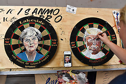 "© Licensed to London News Pictures. 17/08/2018. LONDON, UK. Sign writer Zara Gaze paints images of Theresa May and Donald Trump onto dartboards at ""Letterheads 2018: London Calling"", an international gathering of professional sign writers and lettering artists from over 30 countries.  The event is taking place at the Bargehouse, Oxo Tower Wharf in central London untikl 19 August.  Photo credit: Stephen Chung/LNP"