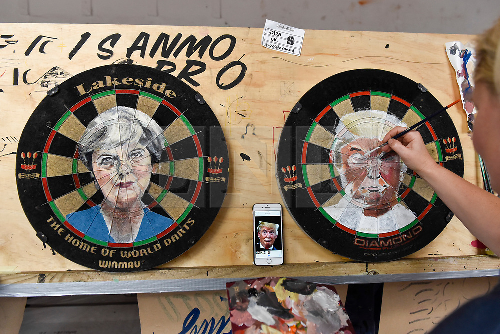 """© Licensed to London News Pictures. 17/08/2018. LONDON, UK. Sign writer Zara Gaze paints images of Theresa May and Donald Trump onto dartboards at """"Letterheads 2018: London Calling"""", an international gathering of professional sign writers and lettering artists from over 30 countries.  The event is taking place at the Bargehouse, Oxo Tower Wharf in central London untikl 19 August.  Photo credit: Stephen Chung/LNP"""