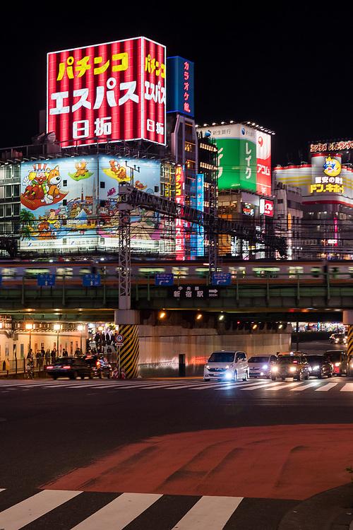 Neon lights, trains & cars at a intersection in Shinjuku, Tokyo.