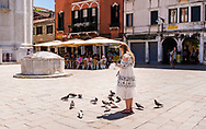 A young woman in a summer dress feeds pigeons in a sunny piazza in Venice, Italy