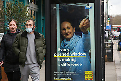 © Licensed to London News Pictures. 06/03/2021. London, UK. A man wearing a protective face covering walks past the government's 'Every opened window is making a difference' awareness poster in north London. The roadmap for the gradual reopening of the Covid-19 lockdown restrictions in England begins from Monday 8 March 2021. Primary and secondary schools will be the first to reopen in England, as the 'stay at home' guidance will change from 29 March 2021. Photo credit: Dinendra Haria/LNP