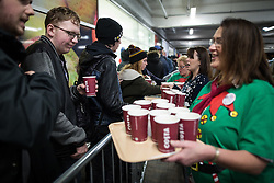 © Licensed to London News Pictures . 27/11/2015 . Salford , UK . A member of staff  hands out hot drinks to people in the queue for Black Friday reductions , at a branch of Tesco in Pendleton , Salford , this morning (Friday 27th November) . Last year (2014) scuffles and fights were reported amongst queuing bargain-hunters . Photo credit: Joel Goodman/LNP