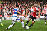 Brentford Forward Oliver Watkins (11) and Queens Park Rangers Defender Darnell Furlong (2) in action during the EFL Sky Bet Championship match between Brentford and Queens Park Rangers at Griffin Park, London, England on 2 March 2019.