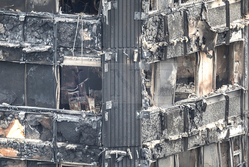 © Licensed to London News Pictures. 18/06/2017. London, UK. Kitchen appliances and the burnt exterior of Grenfell tower block are seen. The blaze engulfed the 27-storey building killing dozens - with 34 people still in hospital, many of whom are in critical condition. The fire brigade say that they don't expect to find anyone else alive. Photo credit: Peter Macdiarmid/LNP