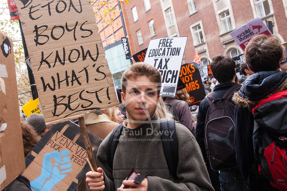 """London, November 19th 2014. Thousands of students march through central London, demanding that education fees are scrapped by the government. PICTURED: With several of the government's top figure having enjoyed an Eton education, a student's placard proclaims ironically, """"Eton Boys Know What's Best""""."""