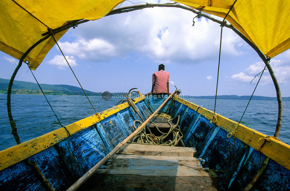 ANDAMAN ISLANDS, INDIA:  A man sits on the bow of a dive boat on its way from South Andaman Island to Rutland Island, Andaman Islands, India.  SCUBA and skin diving is one of the tourist attractions in these remote islands.  The boat being used is a traditional fishing boat hired for the day to transport tourists.