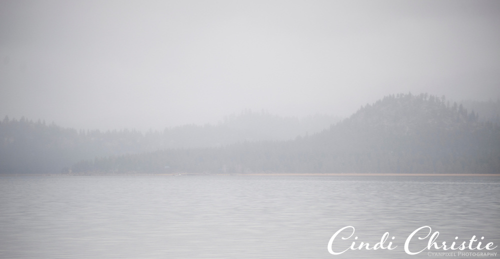 The distant shore is obscured by clouds and snow flurries as seen from South Lake Tahoe, Calif., on Saturday, April 23, 2011.  (© 2011 Cindi Christie/Cyanpixel® Photography)