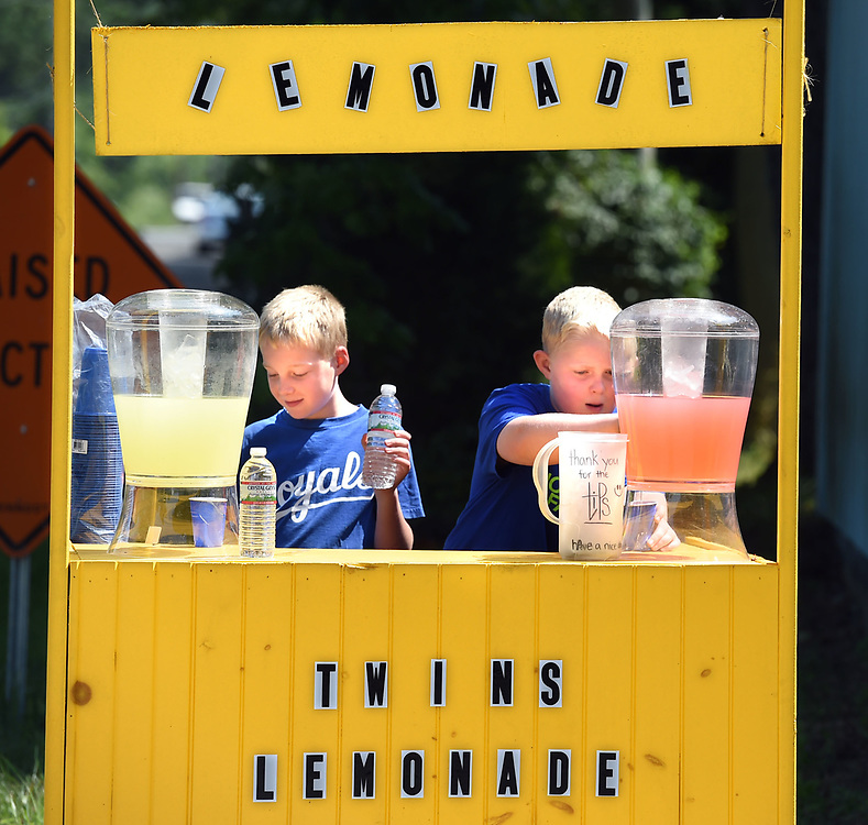 (Mara Lavitt — New Haven Register) <br /> August 4, 2014 Mad, left, and Justin Bailey, age 11 of the Ivoryton section of Essex, have set up their well-appointed lemonade stand outside their father Jeff's business, the Madison Ice House. The two are saving the sales from two different lemonades as well as water, to purchase a tandem bicycle.<br /> mlavitt@newhavenregister.com
