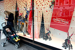 © Licensed to London News Pictures.17/12/2013. London, UK. Shoppers look at festive window display at Peter Jones department  store only a week before Christmas.Photo credit : Peter Kollanyi/LNP