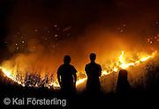 V. 01. Valencia, 13/08/2004. Dos hombres contemplan el frente principal del incendio declarado esta noche (12-08) en la Sierra Calderona. EFE / Kai Försterling.
