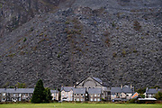 A mountain of slate dominates terraced housing and a church, on 3rd October 2021, in Blaenau Ffestiniog, Gwynedd, Wales. The derelict slate mines around Blaenau Ffestiniog in north Wales were awarded UNESCO World Heritage status in 2021. The industry's heyday was the 1890s when the Welsh slate industry employed approximately 17,000 workers, producing almost 500,000 tonnes of slate a year, around a third of all roofing slate used in the world in the late 19th century. Only 10% of slate was ever of good enough quality and the surrounding mountains now have slate waste and the ruined remains of machinery, workshops and shelters have changed the landscape for square miles.