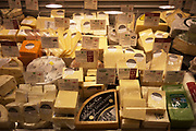 The cheese counter at a Waitrose supermarket. In this section English Cheddar cheeses take up most of the display.
