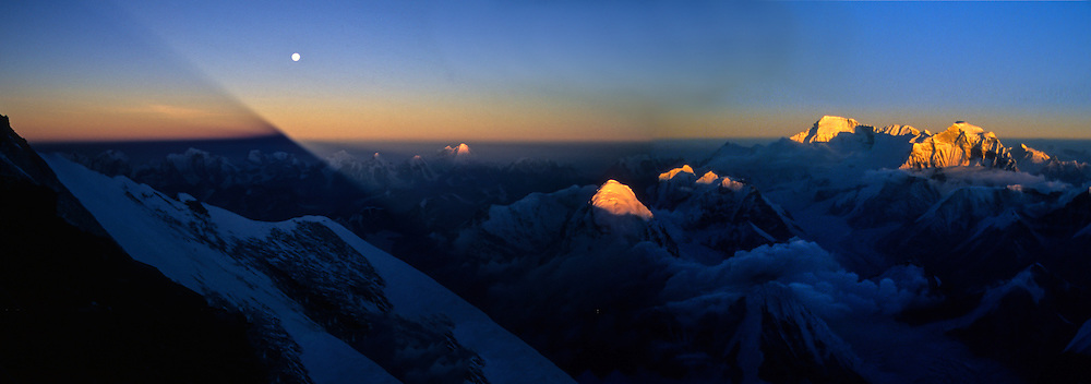 The full moon rises above the shadow of Mount Everest arcing across the spine of the Himalaya; from Camp V at 25,600 feet on the North Ridge, Tibet, China. Prominent, visible peaks are Pumori, Cho Oyu, and Gyachung Kang.