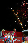 Men's Combined medalists Ted Ligety (gold, center) of the U.S., Ivica Kostelic (silver, far left) of Croatia and Rainer Schoenfelder (bronze, far right) celebrate as fireworks go off overhead during a flower ceremony at Sestriere Colle Tuesday February 14, 2006. American skiier Ted Ligety won the gold medal with combined downhill and slalon times of 3:09.35. Teammate Bode Miller had led all skiiers after the downhill but was disqualified on his first slalom run after stradling a gate..(Photo by Marc Piscotty / © 2006)