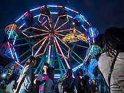 21 NOVEMBER 2015 - BANGKOK, THAILAND: A ferris wheel at the Wat Saket temple fair. Wat Saket is on a man-made hill in the historic section of Bangkok. The temple has golden spire that is 260 feet high which was the highest point in Bangkok for more than 100 years. The temple construction began in the 1800s in the reign of King Rama III and was completed in the reign of King Rama IV. The annual temple fair is held on the 12th lunar month, for nine days around the November full moon. During the fair a red cloth (reminiscent of a monk's robe) is placed around the Golden Mount while the temple grounds hosts Thai traditional theatre, food stalls and traditional shows.     PHOTO BY JACK KURTZ