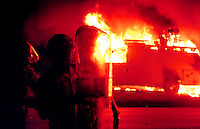 St. Petersburg police move past a burning television news van during a night of riots at 18th Ave and 16th street following the shooting death of TyRon Lewis, Oct. 24, 1996.