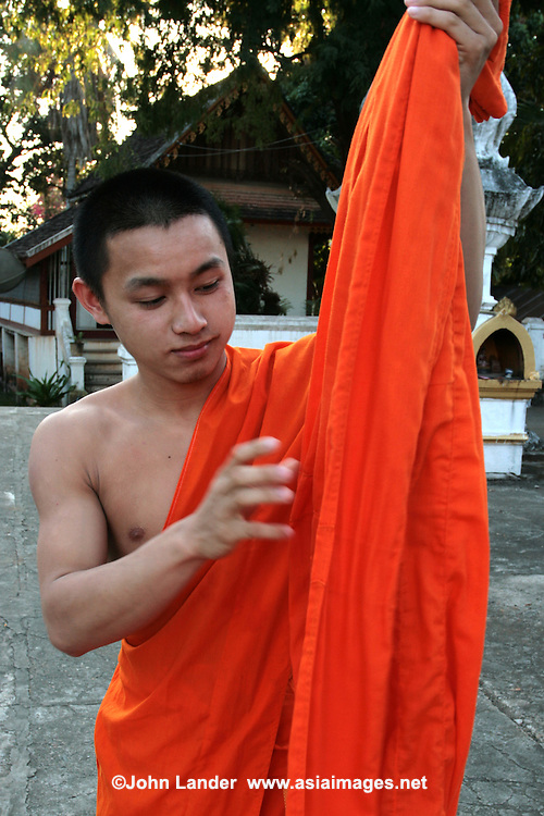 Lao novice monk adjusting his robes at Wat That Noi in Luang Prabang. Buddhism practiced in Laos is a unique version of Theravada Buddhism and is at the root of Lao culture. Buddhism in Laos is often closely tied to animist beliefs and belief in ancestral spirits, particularly in rural areas.