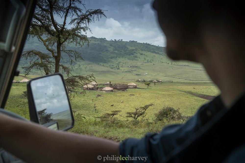 Grass huts of a Masai tribe settlement seen from a safari car, Ngorongoro Conservation area, Tanzania