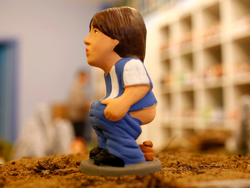 """Torroella de Mongri, Spain, 19 November 2009. .A company in Torroella de Montgrí (Girona, Spain) called """"caganer.com"""" specialized in the production of """"caganers"""" unveiled today  the new figures for Christmas as japanesse soccer player, Shunsuke Nakamura..A """"Caganer"""" is a small figure from Catalonia, usually made of fired clay,  and depicted as squating person in the act defecating. .""""Caganer"""" is Catalan for pooper. It fomrs part of one of the typical figures of  the manger or """"Nativity"""" scene together with Mary, .Joseph and the baby Jesus but hidden in a corner. It is a humorous figure, originally portraying a peasant wearing a .barretina (a red stocking hat), and seems to date from the 18th century when it  was believed that the figure's depositions  .would fertilize the earth to bring a properous year. With  the course of the time, the original  personage of this pooping figure .was  substituted with personalities from the political and sports world and other famous personalities."""