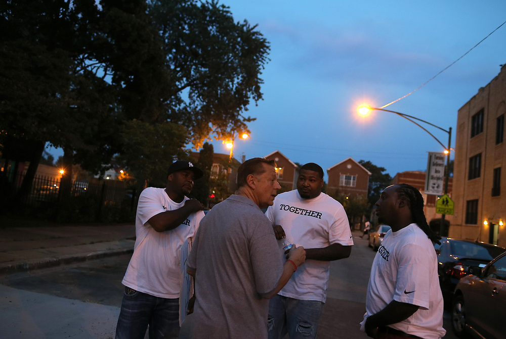 Father Michael Pfleger (2nd L) speaks with participants in a weekly night-time peace march through the streets of a South Side neighborhood in Chicago, Illinois, September 16, 2016.  REUTERS/Jim Young